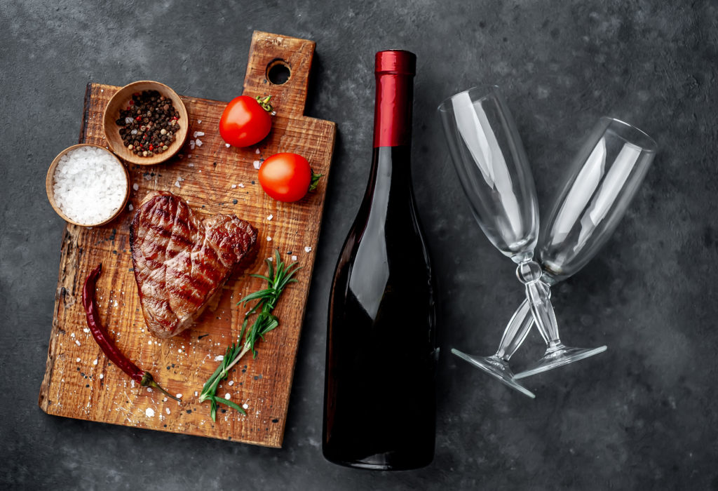 gegrilltes Rindersteak in Form eines Herzens mit Gewürzen und einer Flasche Champagner oder Wein mit zwei Gläsern zum Abendessen zum Valentinstag auf einem steinernen Hintergrund